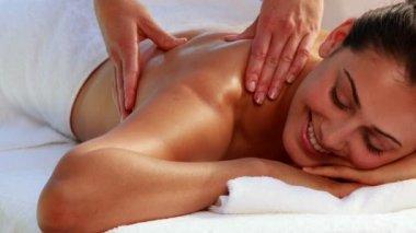 Happy brunette enjoying a massage poolside — Stock Video
