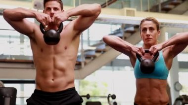 Two fit people lifting kettle bells together — Stock Video
