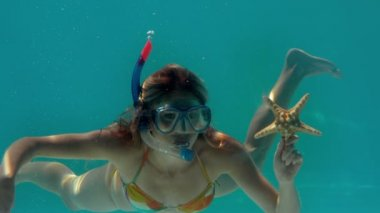 Woman wearing snorkel holding starfish underwater — Stock Video