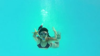 Brunette swimming underwater wearing snorkel holding starfish — Vídeo de stock