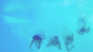 Four friends jumping into swimming pool and waving — 图库视频影像