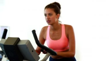 Fit brunette working out on the exercise bike — Wideo stockowe