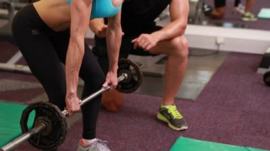 Woman lifting barbell with her trainer — Stok video