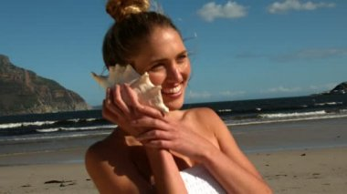 Smiling blonde listening to conch on the beach — Vidéo