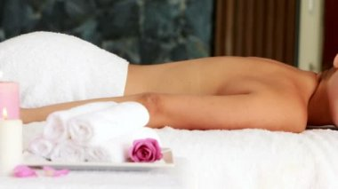 Beautiful brunette lying on massage table smiling at camera — Stock Video