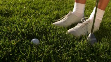 Golf ball falling beside lady golfers feet and club — Stock Video