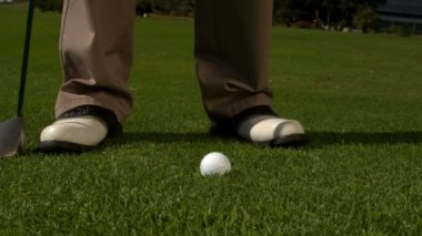 Golf ball falling beside golfers feet and club — Stock Video