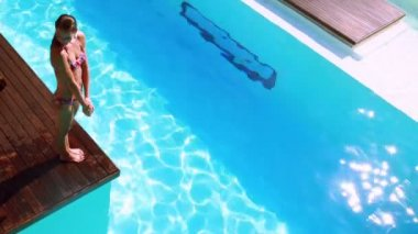 Brunette diving into clear blue pool — Vídeo de stock