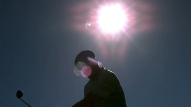 Golfer taking a swing under the sun — Vidéo