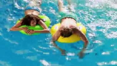 Couple swimming on inflatable rings in the pool — Stock Video