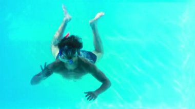 Man in snorkel jumping in swimming pool waving at camera — Stock Video