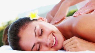 Smiling brunette enjoying a massage poolside — Stock Video