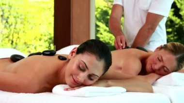Relaxed friends enjoying hot stone massages — Stock Video