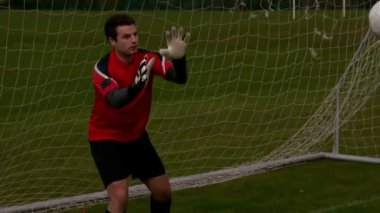 Goalkeeper in red saving a goal — Wideo stockowe