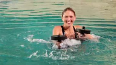 Fit woman doing aqua aerobics in the pool with foam dumbbells — Vídeo de stock