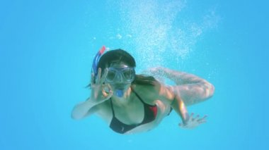 Brunette swimming underwater wearing snorkel making ok sign — Stok video