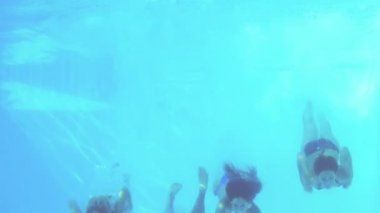 Four friends jumping into swimming pool and waving — Vidéo