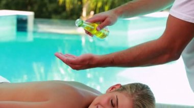 Peaceful blonde getting a massage poolside — Stock Video