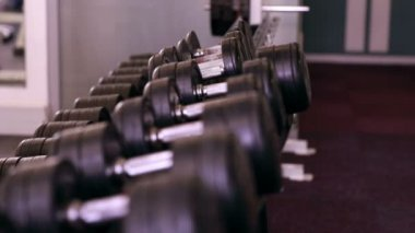 Rack of heavy black dumbbells — Stockvideo