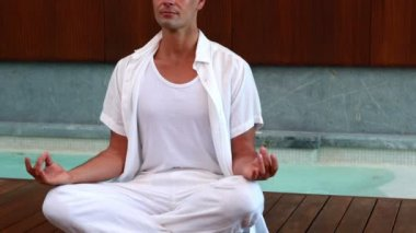Calm man in white sitting in lotus pose — Stock Video