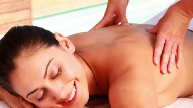 Happy brunette enjoying a massage poolside — Stock Video