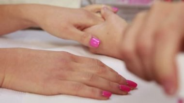 Nail technician applying pink varnish — ストックビデオ