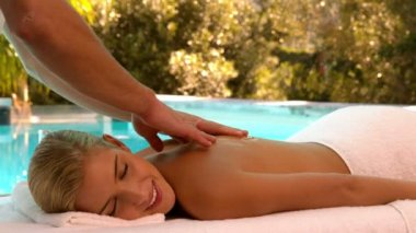 Masseuse rubbing oil into blondes back poolside — Stock Video