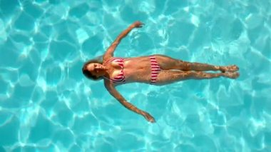 Woman floating in the swimming pool — Stock Video