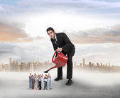 Businessman watering tiny business team — Stock Photo