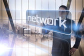 Businessman presenting the word network — Stock Photo