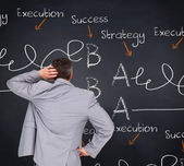 Businessman against blackboard — Stock Photo