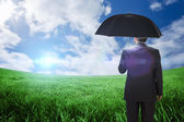Mature businessman holding an umbrella — Stock Photo