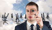 Businessman looking through magnifying glass — Stock Photo
