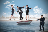 Young businessman pulling a tightrope for business people — Stock Photo