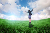 Businesswoman cheering against green field — Stock Photo