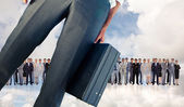 Businessman holding briefcase against business people — Stock Photo
