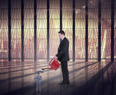 Businessman watering tiny businessman — Stock Photo