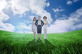 Businesswomen against green field — Stock Photo