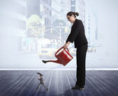 Businesswoman watering tiny businessman — Stock Photo