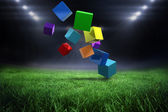 Colourful cubes against football pitch — Stock Photo