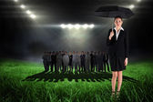 Businesswoman holding umbrella against football pitch — Stock Photo