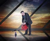 Mature businessman watering tiny businesswoman — Stock Photo