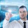 Businessman pointing to word framework — Stock Photo #49990177