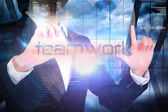 Businesswoman presenting the word teamwork — Photo