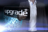 Businessman pointing to word upgrade — Stock Photo