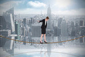 Businesswoman performing balancing act on tightrope — Stock Photo