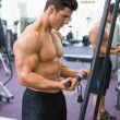 Shirtless muscular man using triceps pull down in gym — Stock Photo #50042437