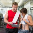 Handsome personal trainer with his client looking at clipboard — Stock Photo #50042719