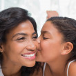 Pretty woman lying on bed with her daughter kissing cheek — Stock Photo #50042769