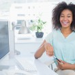 Casual businesswoman smiling at camera at her desk — Stock Photo #50043181